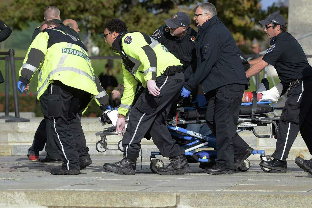 Paramedics and police pull a victim away from the Canadian War Memorial in Ottawa on Wednesday Oct. 22, 2014. A soldier standing guard at the National War Memorial in Ottawa has been shot by an unknown gunman and people report hearing gunfire inside the halls of Parliament.