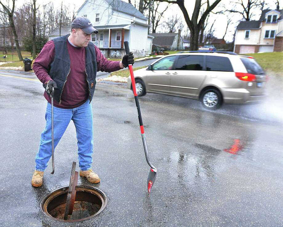 Joe Augeri, the Assistant Director of Middletown Public Works Department keeps an eye on the water running over Highland Avenue as he checks the drain on Ward Street Monday afternoon in preparation of the icy condidtions predicted Tuesday. Photo: Catherine Avalone - The Middletown Press / TheMiddletownPress