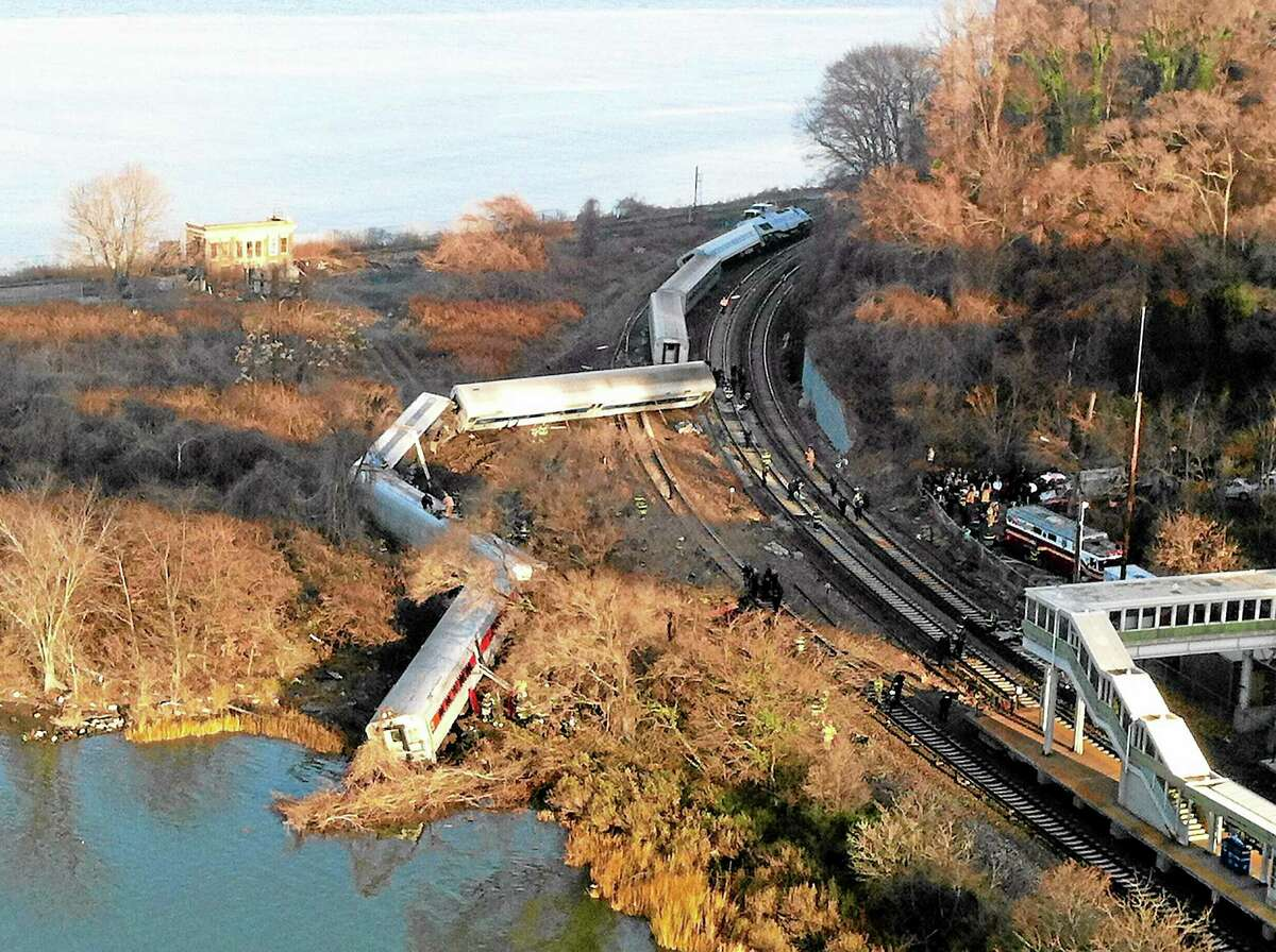 """Cars from a Metro-North passenger train are scattered after the train derailed in the Bronx borough of New York, Sunday, Dec. 1, 2013. The Fire Department of New York says there are """"multiple injuries"""" in the train derailment, and 130 firefighters are on the scene. Metropolitan Transportation Authority police say the train derailed near the Spuyten Duyvil station. (AP Photo/Edwin Valero)"""
