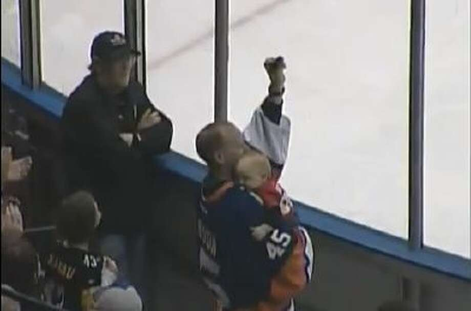A hockey fan catches a puck while holding onto a baby.