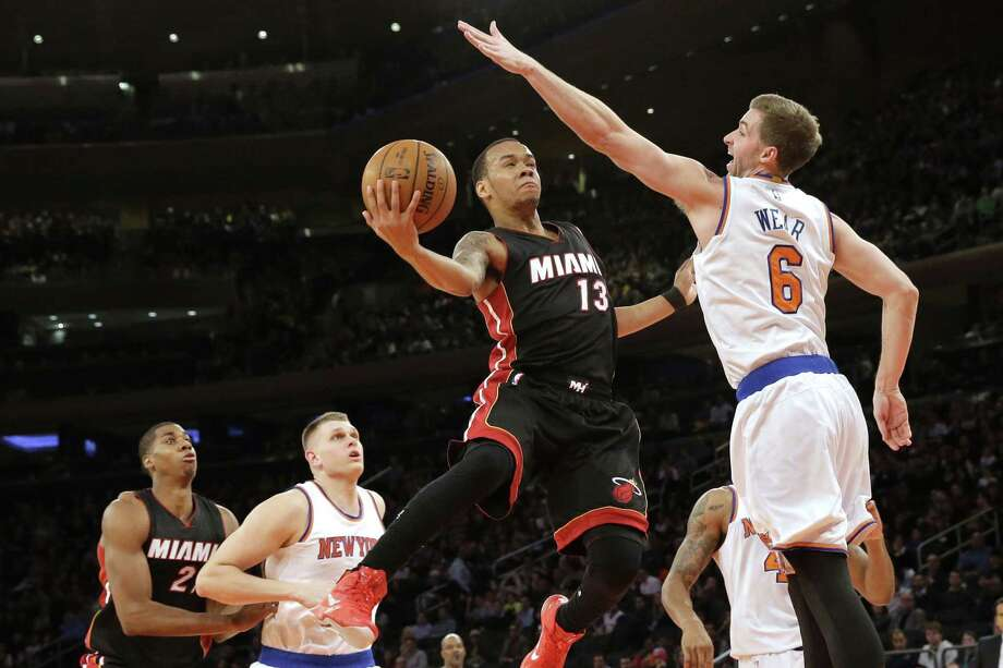 Miami Heat guard Shabazz Napier goes up against Knicks forward Travis Wear during the first half of Friday's game at Madison Square Garden in New York. Photo: Mary Altaffer — The Associated Press  / AP