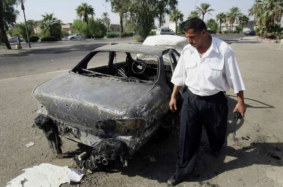FILE - In this Sept. 25, 2007 file photo, an Iraqi traffic policeman inspects a car destroyed by a Blackwater security detail in al-Nisoor Square in Baghdad, Iraq. A federal jury reached a verdict Wednesday in the case of four former Blackwater security guards on trial in the shootings of more than 30 Iraqi citizens in the heart of Baghdad. The verdicts were to be read during a late-morning court session. The shootings triggered an international uproar over the role of defense contractors in urban warfare. (AP Photo/Khalid Mohammed, File) Photo: AP / AP