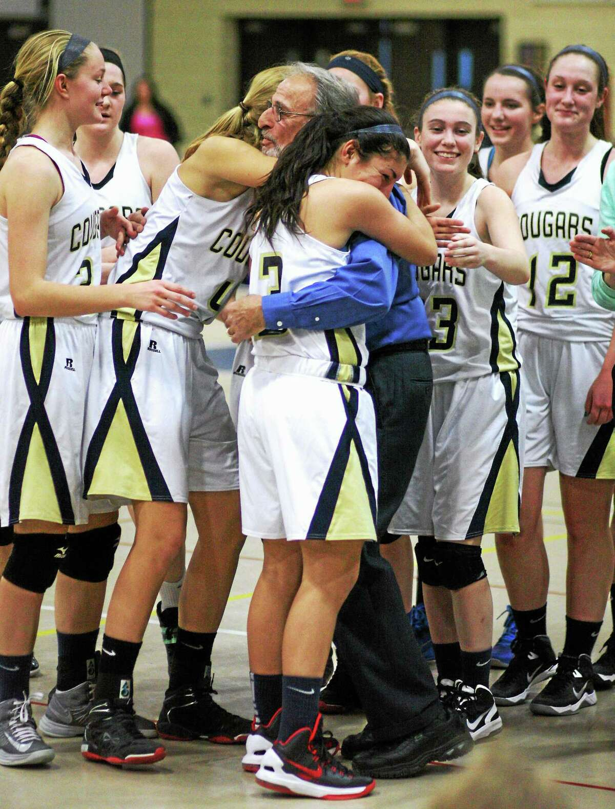 Eric Anderson — Special to Middletown Press Haddam-Killingworth seniors Kiley Anderson (4) and Maya Savino (3) give Cougars coach Jim Bombaci a hug following H-K's 68-44 win against Hyde on Saturday. It was Bombaci's 500th career victory.