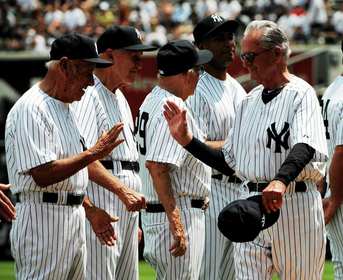 Former New York Yankees second baseman Jerry Coleman, right, reacts with other players during Old Timers' Day ceremonies Sunday, June 26, 2011 at Yankee Stadium in New York. (AP Photo/Bill Kostroun)