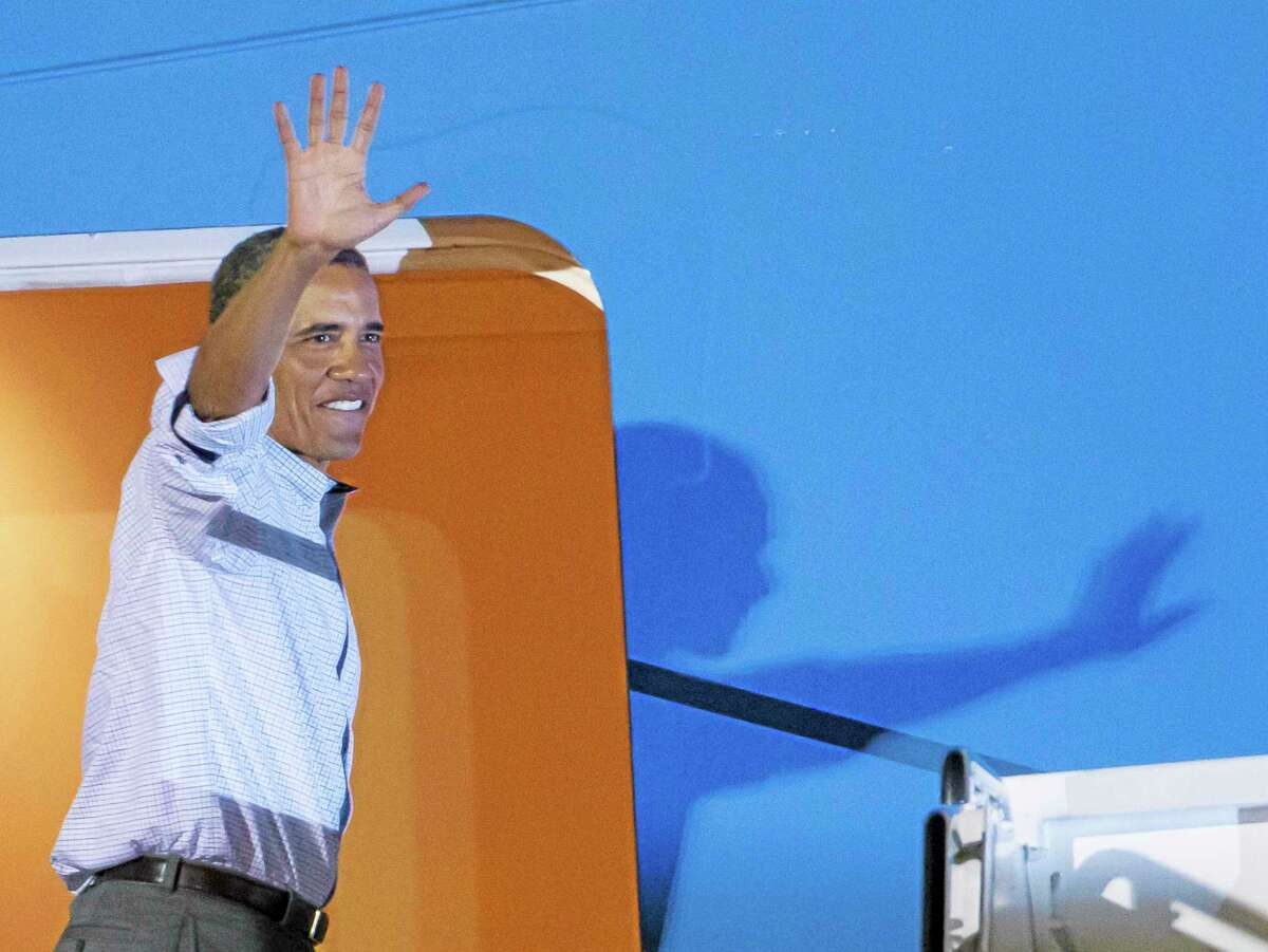 President Barack Obama waves to various Hawaii dignetaries before boarding Air Force One at Joint Base Pearl Harbor-Hickam to return to Washington Saturday, Jan. 4, 2014, in Honolulu. The President along with his family spent the last two weeks vacationing in Kailua, Hawaii. AP Photo/Eugene Tanner