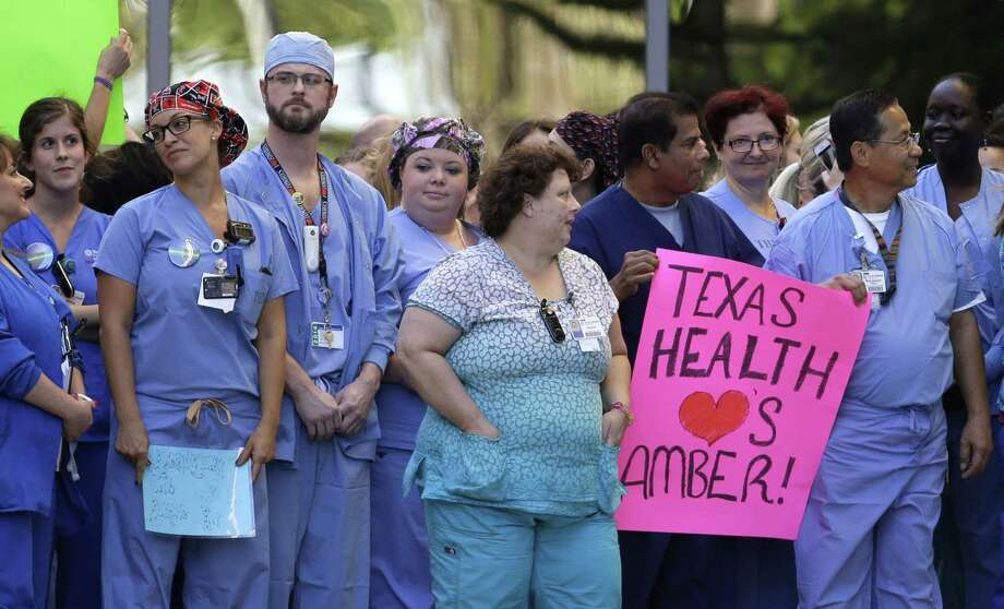 FILE - In this Oct. 16, 2014 file photo, Texas Health Presbyterian Hospital Dallas staff line the drive that exits the emergency room as they wait for an ambulance carrying Ebola patient Nina Pham to depart, in Dallas. Pham, a nurse at the hospital was diagnosed with the virus after caring for Thomas Eric Duncan who died of the same virus. Amber Vinson, another nurse diagnosed, was taken to a similar location in Atlanta. For all the strengths of Texas Health Presbyterian Hospital Dallas, the first U.S.-diagnosed Ebola patient walked through the seemingly weakest link in its medical armor: the emergency room. Photo: (AP Photo/Tony Gutierrez, File) / AP