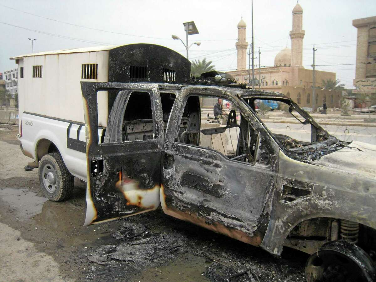 The Prophet Muhammad Mosque looks over a burned police vehicle left in the main street of Fallujah after clashes between Iraqi security forces and al-Qaeda fighters in Fallujah, 40 miles (65 kilometers) west of Baghdad, Iraq, Sunday. AP Photo