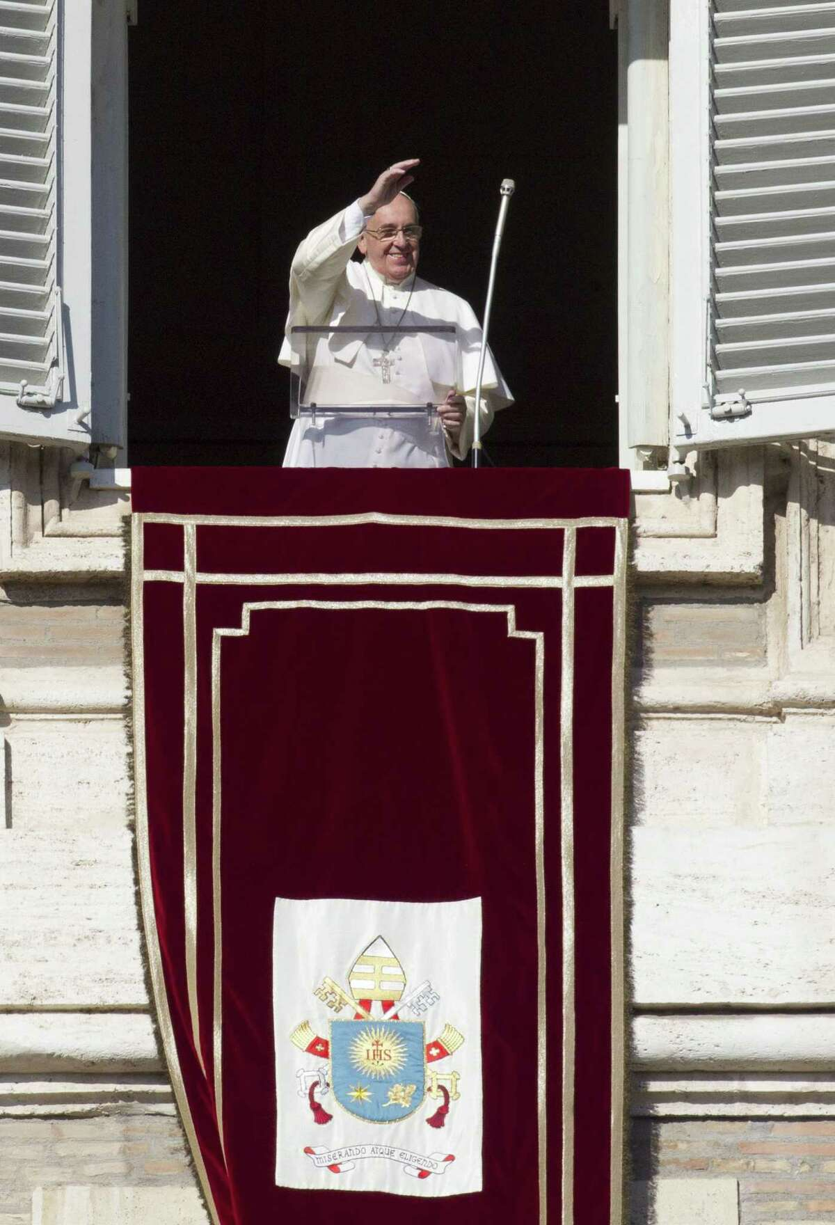 In this January file photo, Pope Francis waves to faithful as he arrives to celebrate the Angelus noon prayer from his studio window overlooking St. Peter's square at the Vatican.