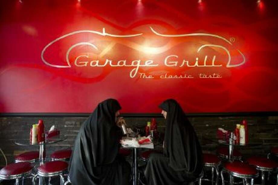 Iranian women eat burger at Garage Grill restaurant in Tehran, Iran on Dec 18, 2013.