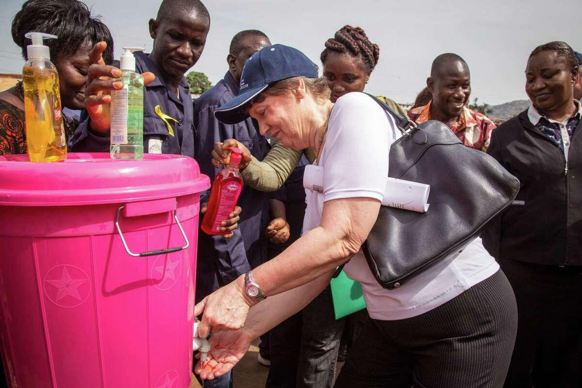 Former Prime Minister of New Zealand Helen Clark and Administrator of the United Nations Development Programme (UNDP) washes her hands as she visit communities affected by the Ebola virus in Freetown, Sierra Leone, Tuesday, Feb. 17, 2015. Hand washing and basic sanitation has been a key factor in the fight against the Ebola Virus in West Africa. (AP Photo/Michael Duff)