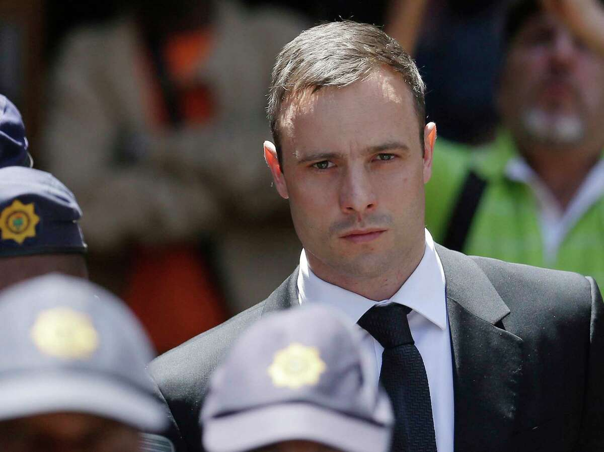 """FILE - In this Friday, Oct. 17, 2014 file photo, Oscar Pistorius is escorted by police officers as he leaves the high court in Pretoria, South Africa. A South African official says Oscar Pistorius has been released from prison and placed under house arrest. Manelisi Wolela, a spokesman for South Africa's correctional services department, said the double-amputee Olympic runner who fatally shot his girlfriend on Valentine's Day 2013 was put under """"correctional supervision"""" late on Monday, Oct. 19, 2015. (AP Photo/Themba Hadebe, File)"""