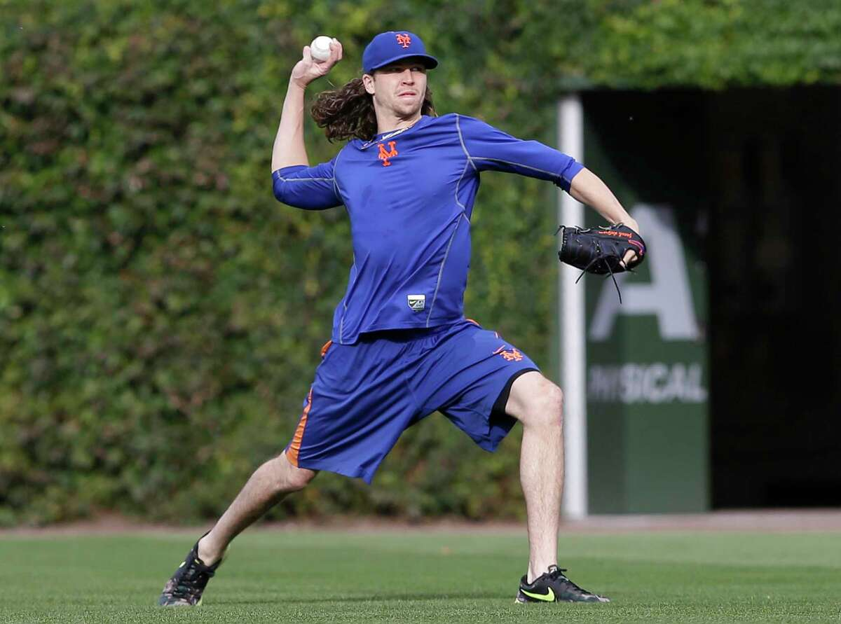 Jacob deGrom throws during a team workout Monday at Wrigley Field.