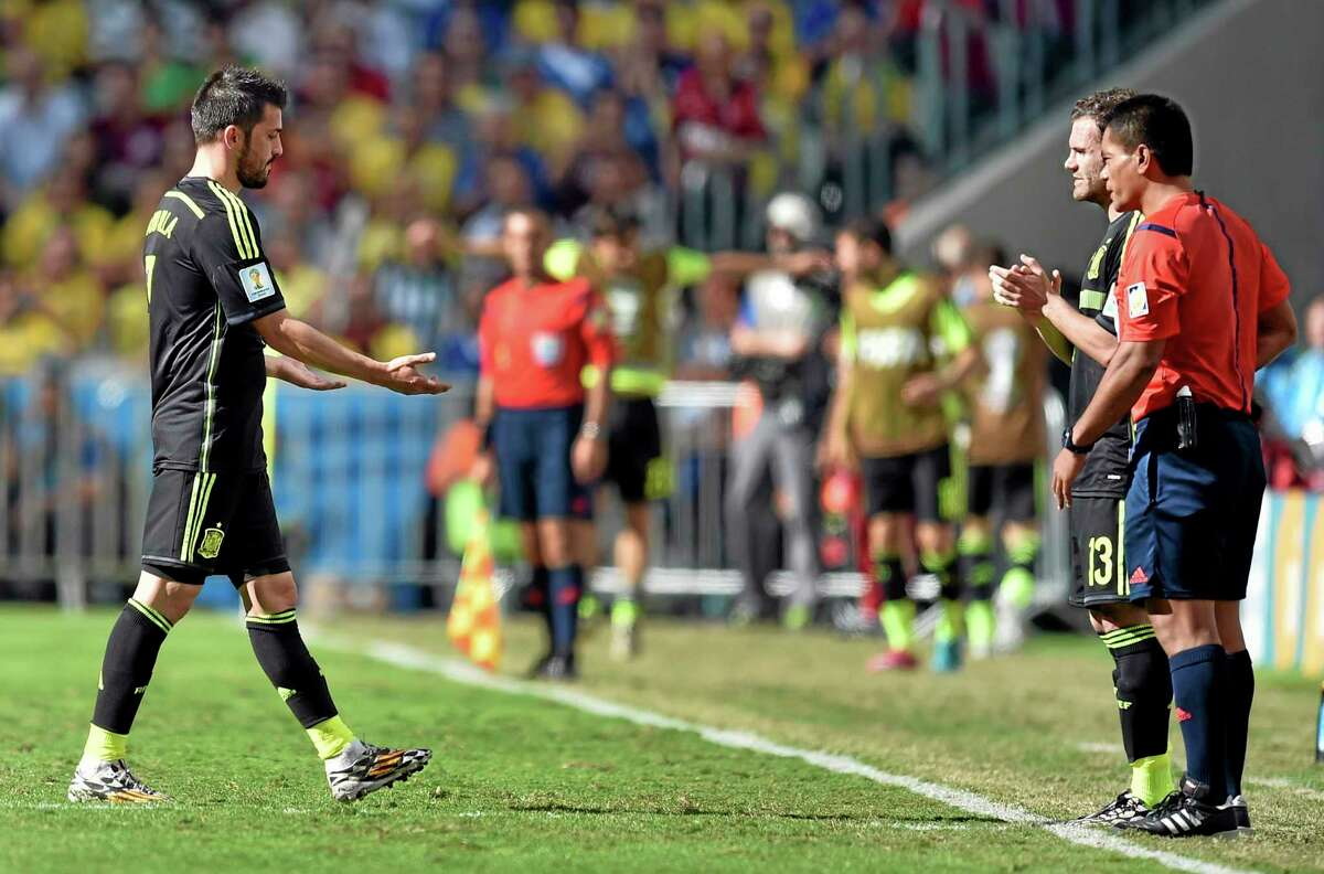 Spain's David Villa, left, leaves the field to be substituted by Juan Mata during the group B World Cup soccer match between Australia and Spain at the Arena da Baixada in Curitiba, Brazil, Monday, June 23, 2014. (AP Photo/Martin Meissner)
