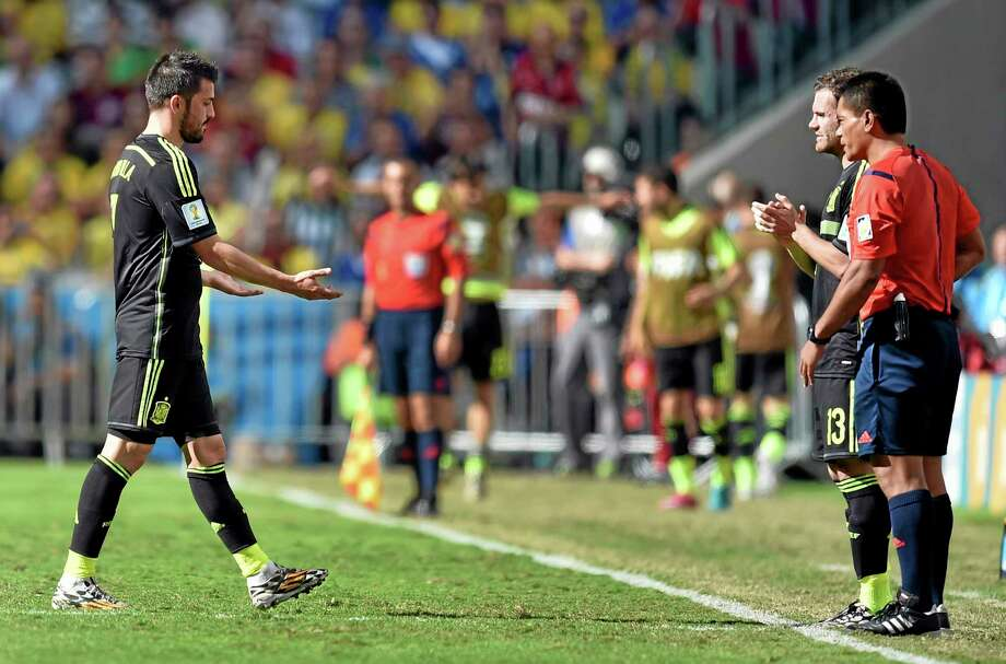 Spain's David Villa, left, leaves the field to be substituted by Juan Mata during the group B World Cup soccer match between Australia and Spain at the Arena da Baixada in Curitiba, Brazil, Monday, June 23, 2014. (AP Photo/Martin Meissner) Photo: AP / AP