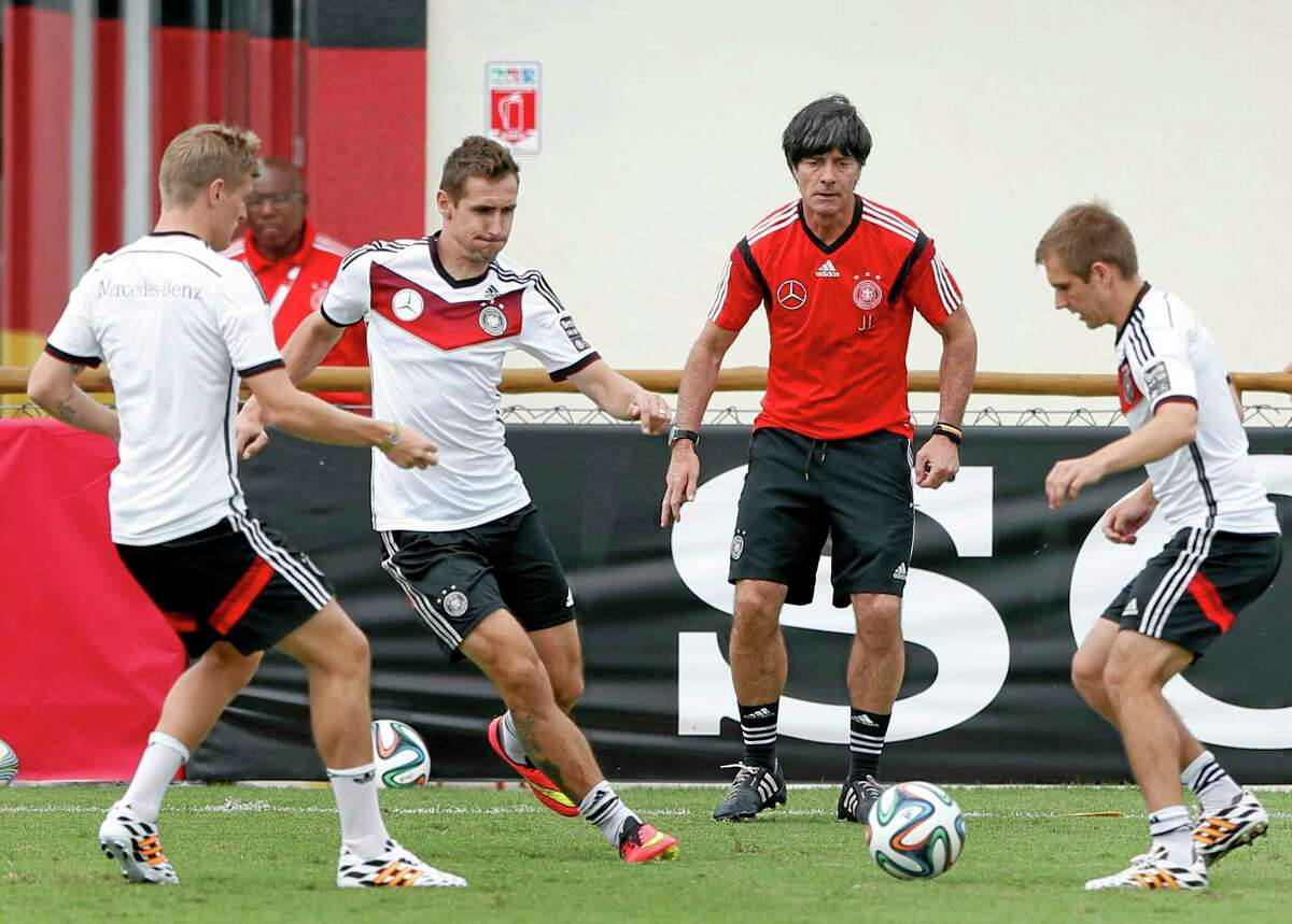 German national soccer players Tonis Kroos, from left, Miroslav Klose, head coach Joachim Loew and captain Philipp Lahm challenge for the ball during a training session Monday.