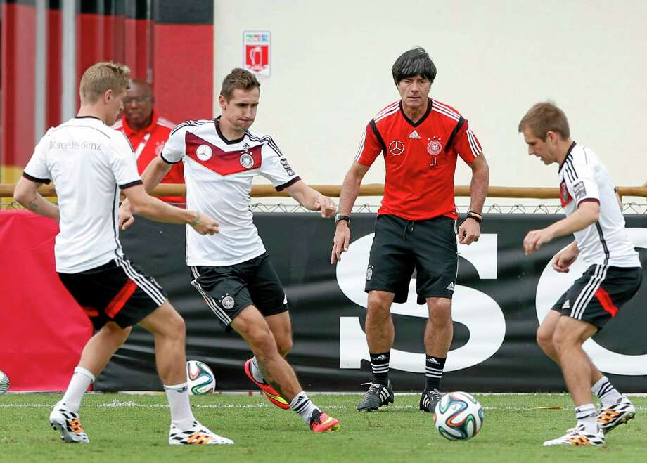 German national soccer players Tonis Kroos, from left, Miroslav Klose, head coach Joachim Loew and captain Philipp Lahm challenge for the ball during a training session Monday. Photo: Matthias Schrader — The Associated Press  / AP