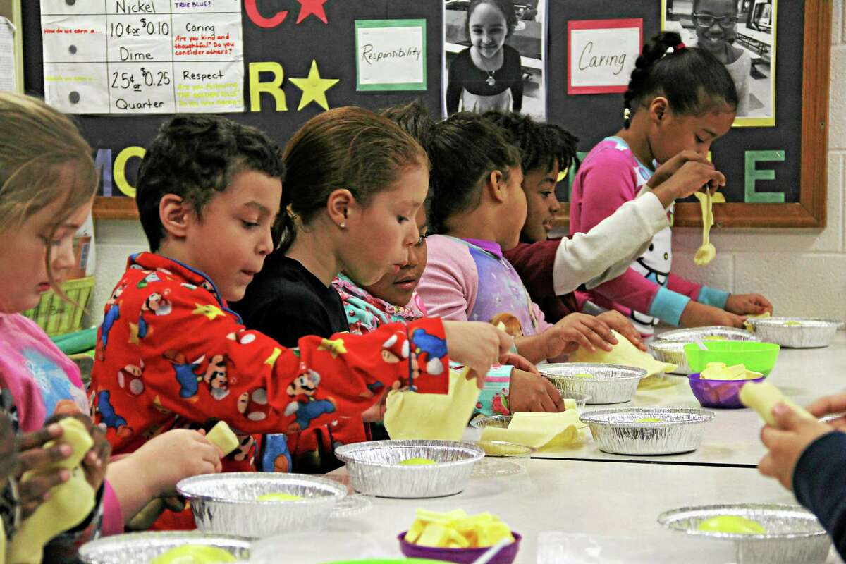 Second-graders at Macdonough Elementary School prepare apple dumplings with help from the Middletown Rotary Club's newest literacy project.