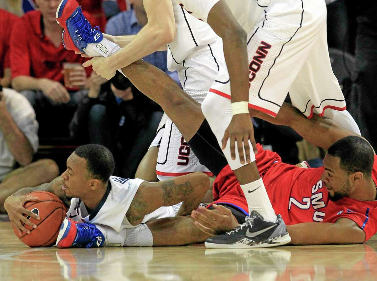UConn guard Ryan Boatright, left, grabs a loose ball as SMU forward Shawn Williams joins him on the floor during the first half of the Mustangs' 74-65 win over the 17th-ranked Huskies on Saturday in Dallas.