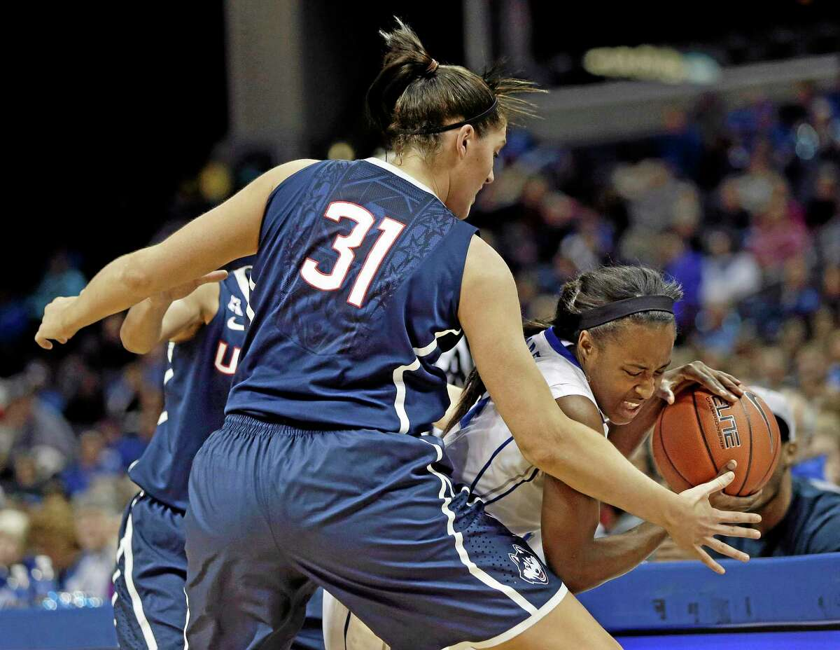 UConn center Stefanie Dolson blocks the path of Memphis guard Devin Mack, right, during the first half of the top-ranked Huskies' 90-49 win on Saturday afternoon in Memphis, Tenn.