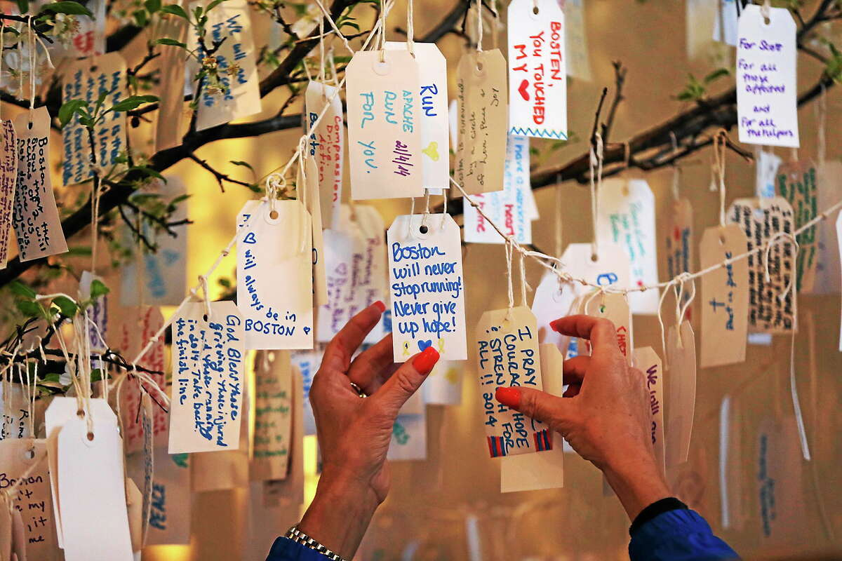 """A visitor hangs a message on a tree at the """"Dear Boston"""" exhibit at the Boston Public Library on April 20, 2014 in Boston. The exhibit features a collection of items from the marathon bombing memorial."""