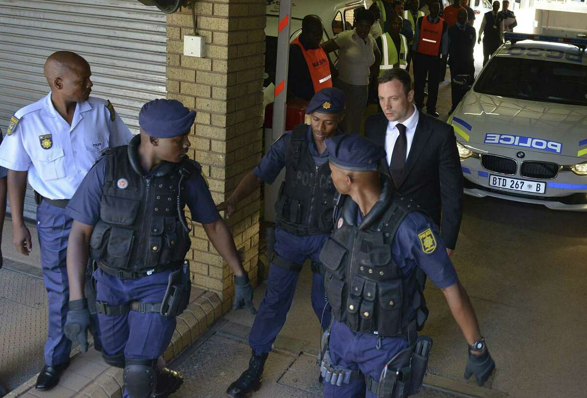 Oscar Pistorius, rear right, is led to a awaiting police vehicle to be taken to prison outside the court in Pretoria, South Africa on Oct. 21, 2014.