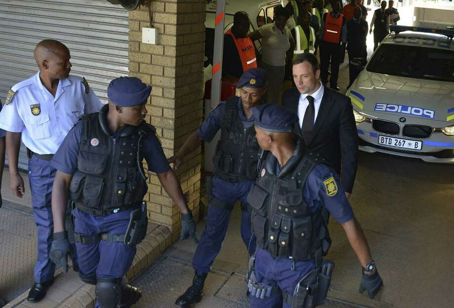 Oscar Pistorius, rear right, is led to a awaiting police vehicle to be taken to prison outside the court in Pretoria, South Africa on Oct. 21, 2014. Photo: AP Photo/Antoine De Ras, Independent Newspapers  / INDEPENDENT NEWSPAPERS