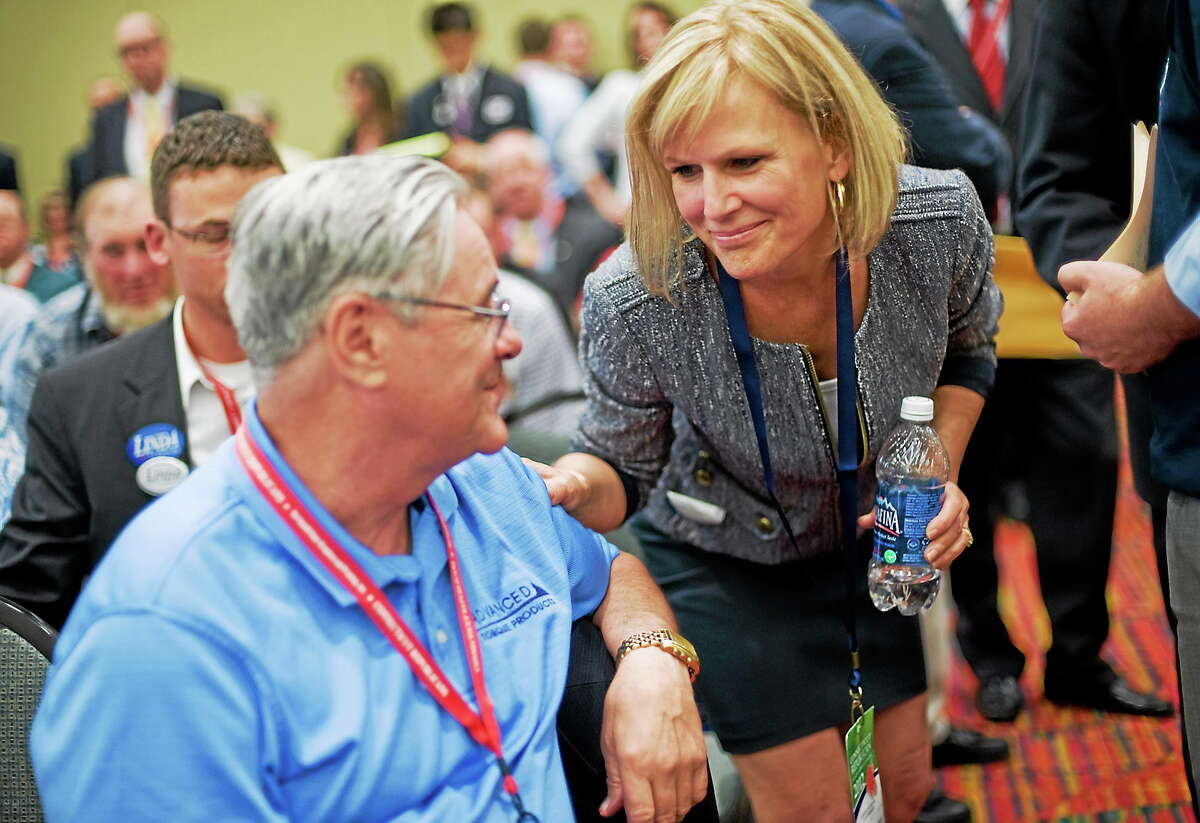 Lisa Wilson-Foley, right, talks with delegate George Castle of Plymouth at the Republican state convention in Hartford, Conn. on May 18, 2012.