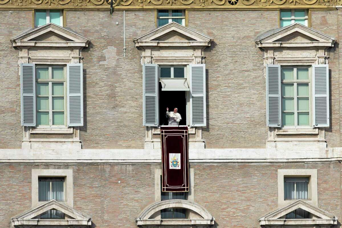 """Pope Francis delivers his blessing during the Angelus noon prayer he celebrated from the window of his studio overlooking St. Peter's Square at the Vatican, Wednesday, Jan. 1, 2014. """"We are all children of one heavenly father, we belong to the same human family and we share a common destiny,"""" Francis said, as tens of thousands of faithful, tourists and Romans jammed St. Peter's Square. (AP Photo/Andrew Medichini)"""