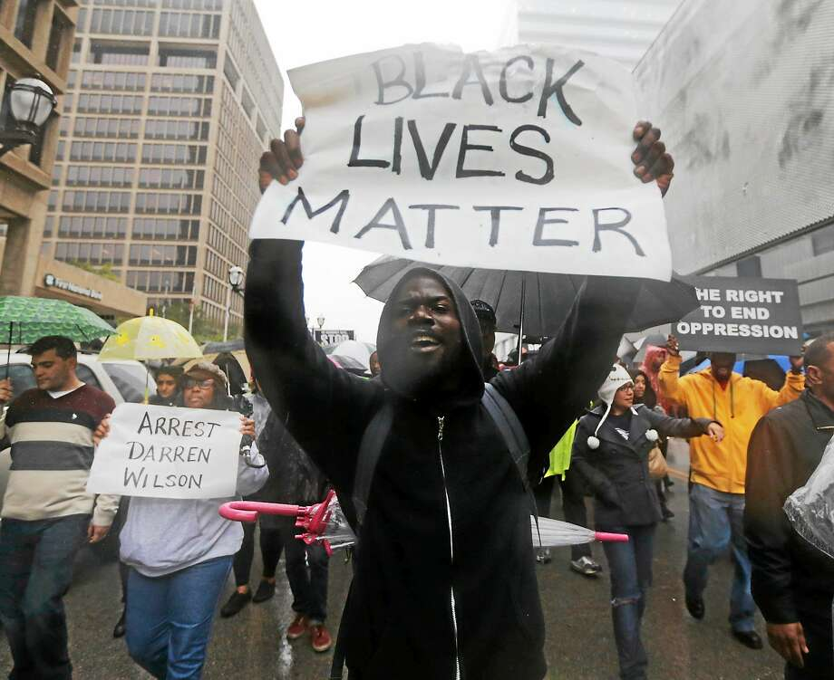 Protesters carry signs as they march in the streets of Clayton, Mo. on Oct. 10, 2014 near the St. Louis County Courthouse during a protest against the police shooting of unarmed black 18-year-old Michael Brown in Ferguson, Mo. Photo: AP Photo/Charles Rex Arbogast  / AP