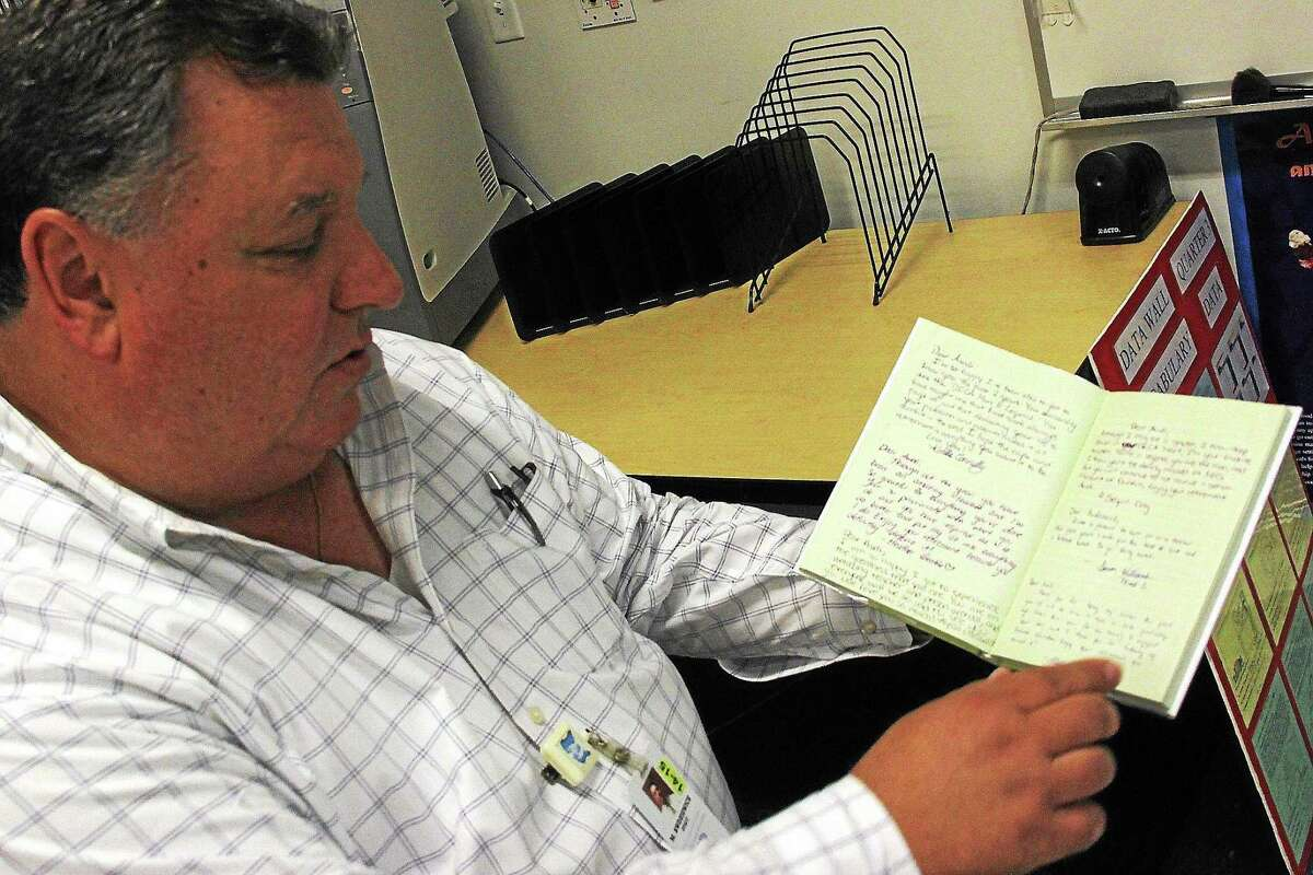 Middletown High School teacher Mike Awdziewicz retired this month after 36 years of work that includes the creation of the city's chapter of the highly successful Distributive Education Club of America business club. Here, he looks over the book of messages from students and staff that's set up like a novel.