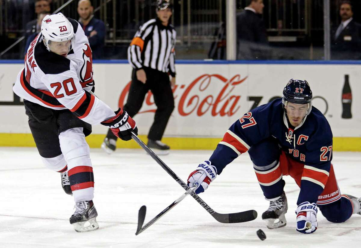 Devils right wing Lee Stempniak, left, takes a shot defended by Rangers defenseman Ryan McDonagh during the third period Sunday.