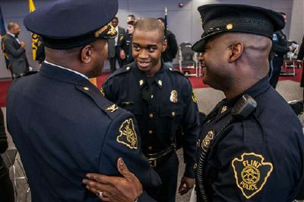 A new officer is congratulated in Flint, Mich. Some cities, like Salt Lake City, are looking to give their police officers more training.