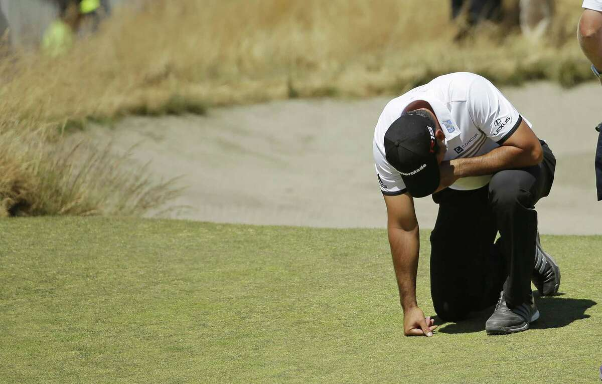 Jason Day kneels while waiting to putt on the ninth hole after having collapsed during the second round of the U.S. Open on Friday at Chambers Bay in University Place, Wash.