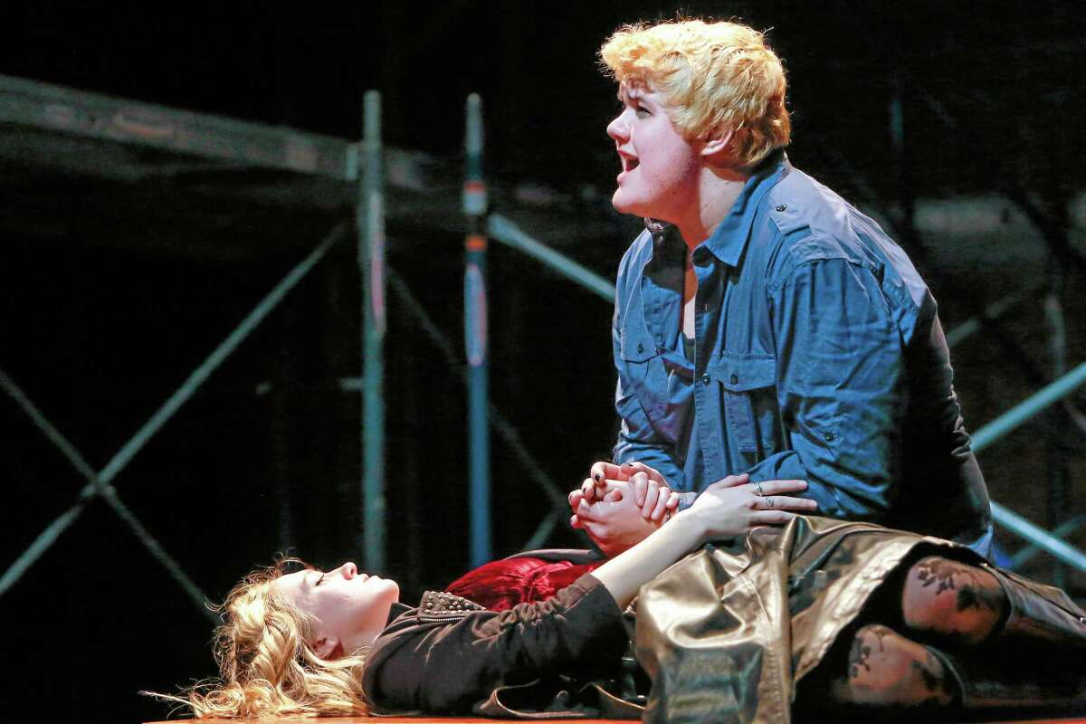 """Musician Roger Davis, played by Mark Sumner, grieves over the near death of his girlfriend Mimi Marquez, played by Maya Eriksen, in Middletown High's 2013 drama club production of """"Rent."""""""