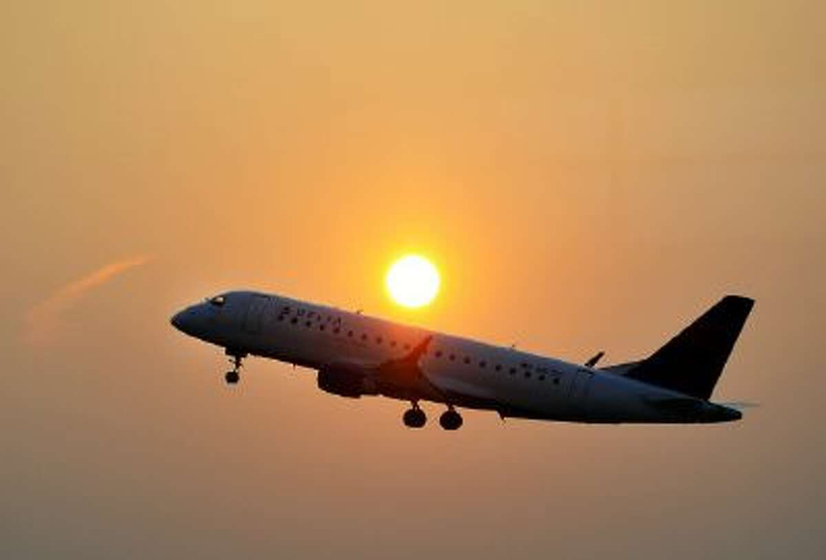 A Delta airline's aircraft takes off from the Ronald Reagan National airport as the sun rises in Washington, DC, on June 9, 2011.
