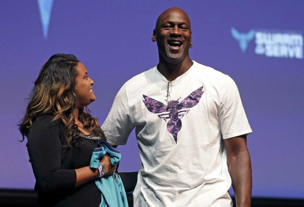 """Charlotte Hornets owner Michael Jordan, right, shares a laugh with Tomeka Dossa Scott, left, during a news conference to announce the team's """"Day of Service"""" benefiting military personnel on Monday in Charlotte, N.C."""