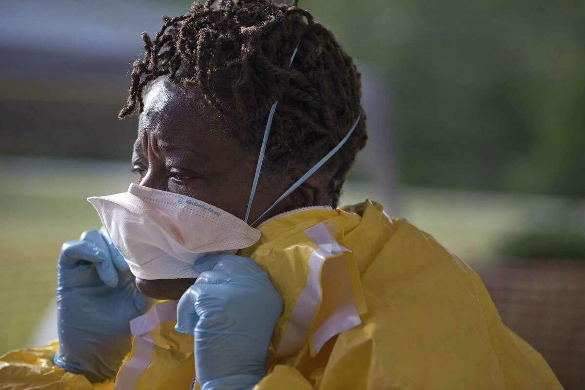 FILE -In this Monday, Oct. 6, 2014 file photo, licensed clinician Roseda Marshall, of Liberia, disrobes after a simulated training session, in Anniston, Ala.