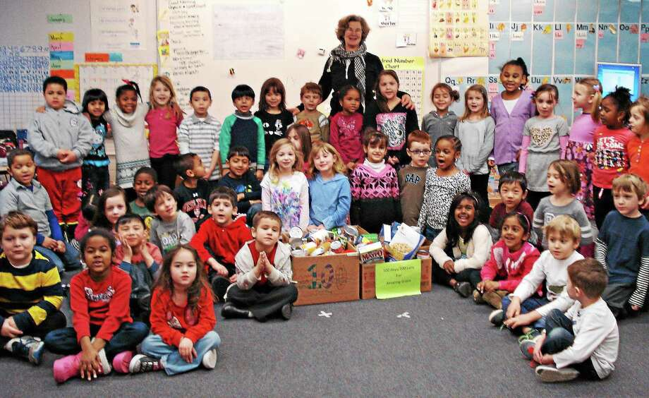 Longtime school nurse Kathy Ellis joins three kindergarten classes that gathered 100 cans of food this month for those in need. The students also challenged other classes in the school to do the same. Photo: Courtesy Lawrence Elementary School