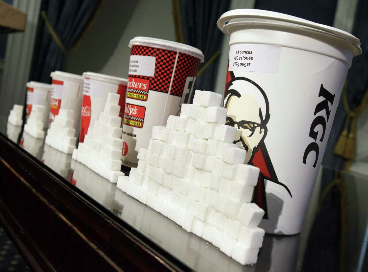 FILE - This Thursday, May 31, 2012 file photo shows a display of various size soft drink cups next to stacks of sugar cubes at a news conference at New York's City Hall.