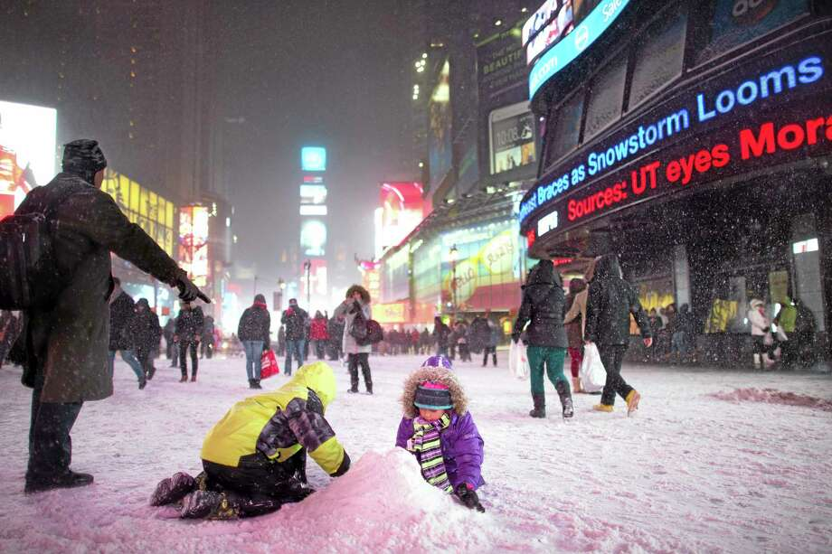 Children make a snow pile in Times Square, during a snowstorm, Thursday, Jan. 2, 2014, in New York. The storm is expected to bring snow, stiff winds and punishing cold into the Northeast. (AP Photo/John Minchillo) Photo: AP / FR170537 AP
