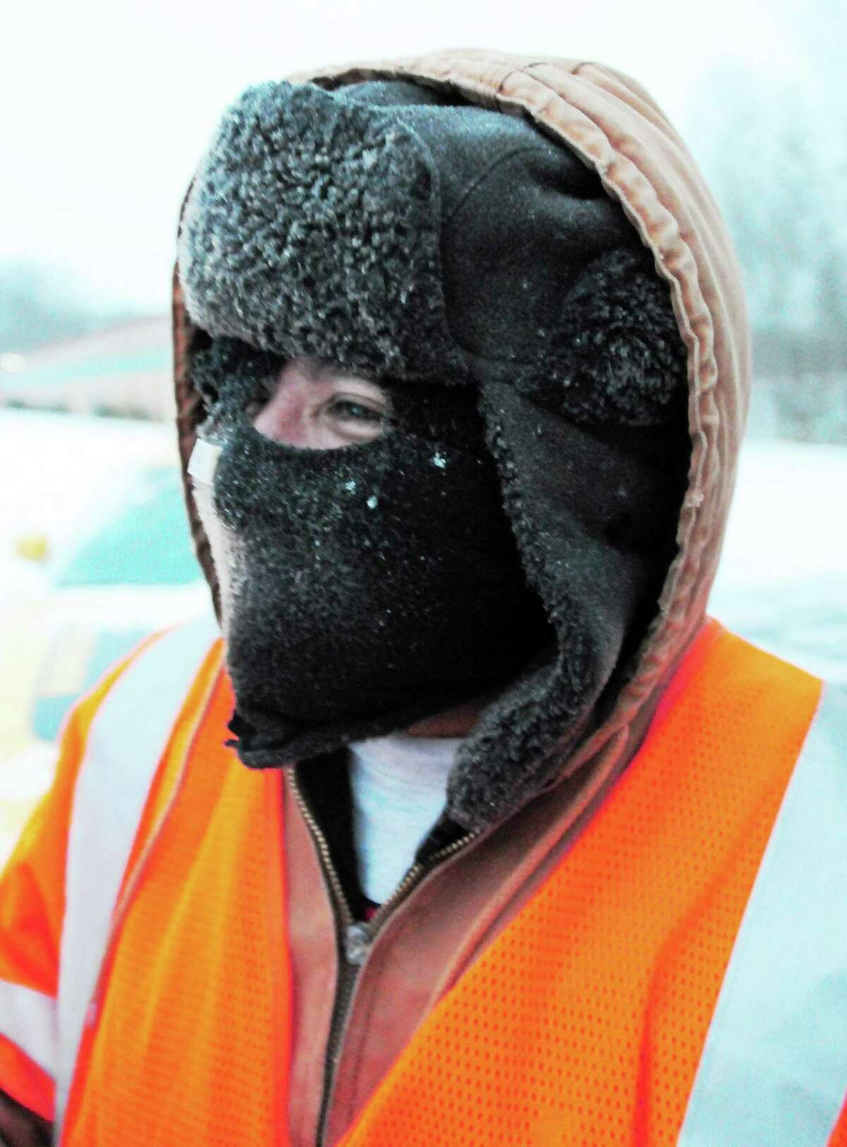 An employee for DeMars Landscaping of Branford faces the cold with warm head gear as he shovels snow in a shopping plaza at 365 East Main St. Friday morning.