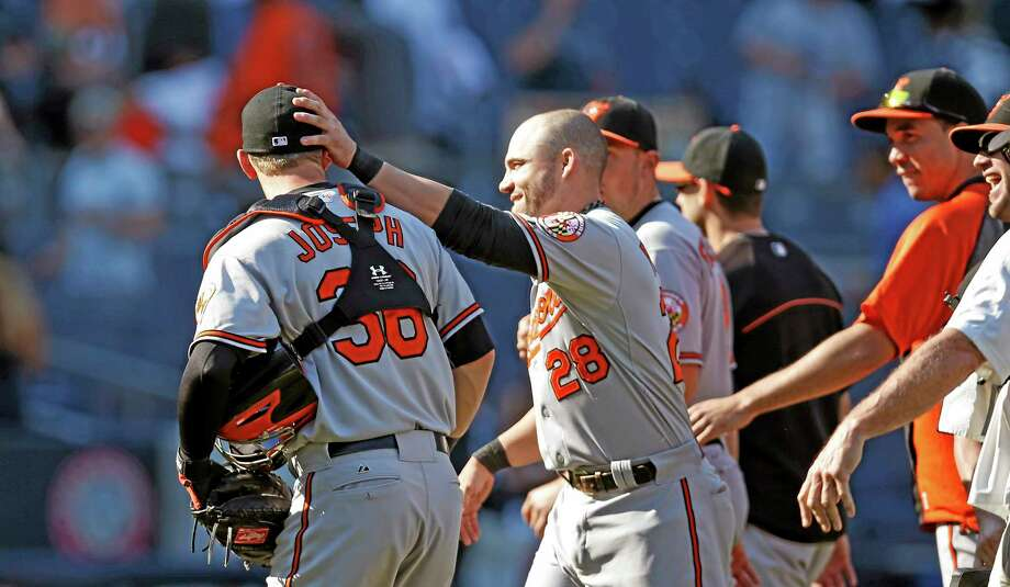 Steve Pearce (28) pats Orioles catcher Caleb Joseph (36) on the back of the head after Baltimore's 8-0 victory over the Yankees on Sunday at Yankee Stadium in New York. Photo: Kathy Willens — The Associated Press  / AP