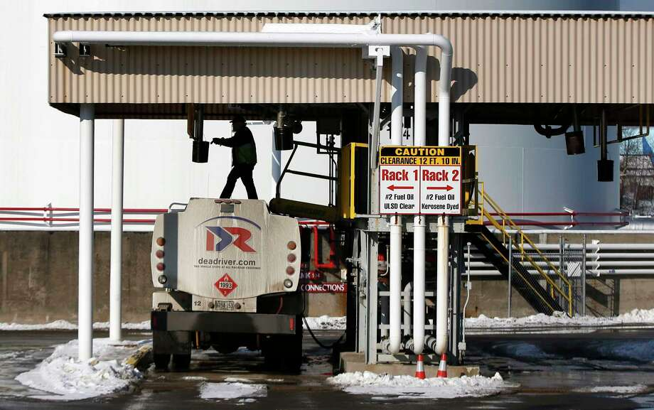 In this Jan. 16, 2015 photo, a driver for an oil delivery company fills his truck at the Sprague terminal in South Portland, Maine. New England is getting another break on heating oil prices this winter, with potential savings of hundreds of dollars per customer, providing breathing room for a region with some of the nation's highest energy costs. But some officials worry lower prices will lead to complacency on efforts to improve efficiency. Photo: AP Photo/Robert F. Bukaty, File  / AP