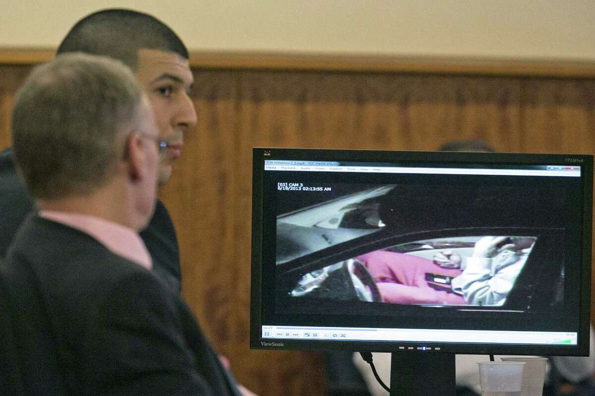 Aaron Hernandez, rear, and his attorney Charles Rankin watch surveillance video of Hernandez handling cell phones during his murder trial on Tuesday at the Bristol County Superior Court in Fall River, Mass.