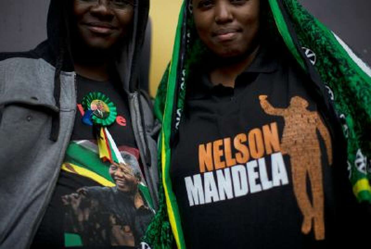 Mourners display their Nelson Mandela t-shirts as they wait for the memorial service for former South African president Nelson Mandela at the FNB Stadium in Soweto near Johannesburg, Tuesday, Dec. 10, 2013.