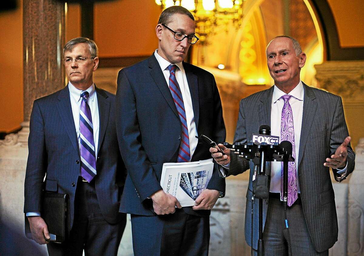 Chief of Staff Mark Ojakian, right answers questions from the media as Budget Director Benjamin Barnes, center, and Department of Transportation Commissioner, James P. Redeker, left, listen, at the state Capitol on Feb. 18, 2015 in Hartford, Conn.