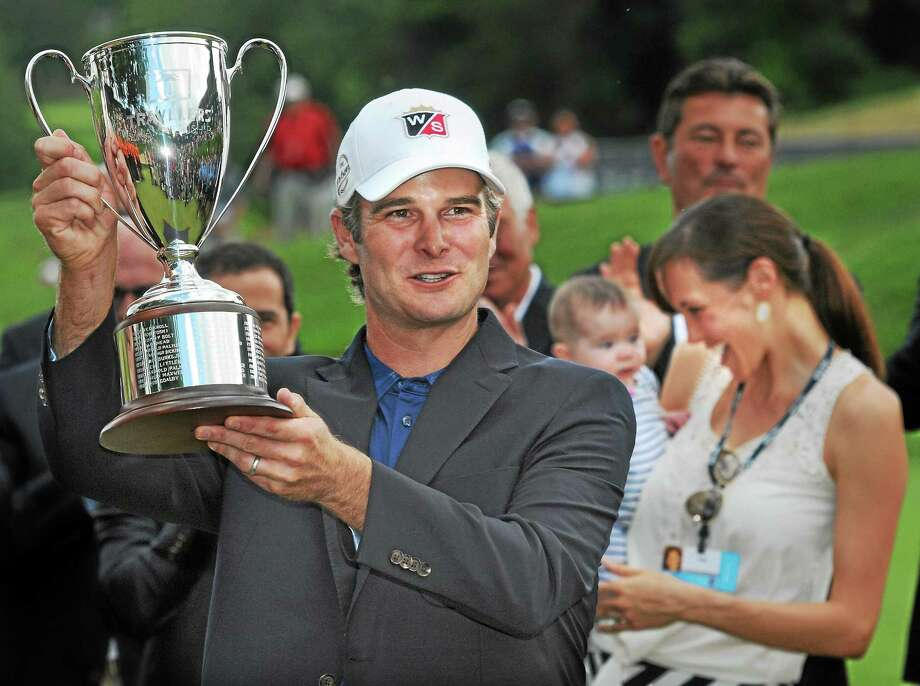 Kevin Streelman poses with the Travelers Championship trophy after birdieing the final seven holes and finishing 15-under on Sunday in Cromwell. In the background are his wife, Courtney, and 6-month-old daughter, Sophia. Photo: Mara Lavitt — Register  / Mara Lavitt