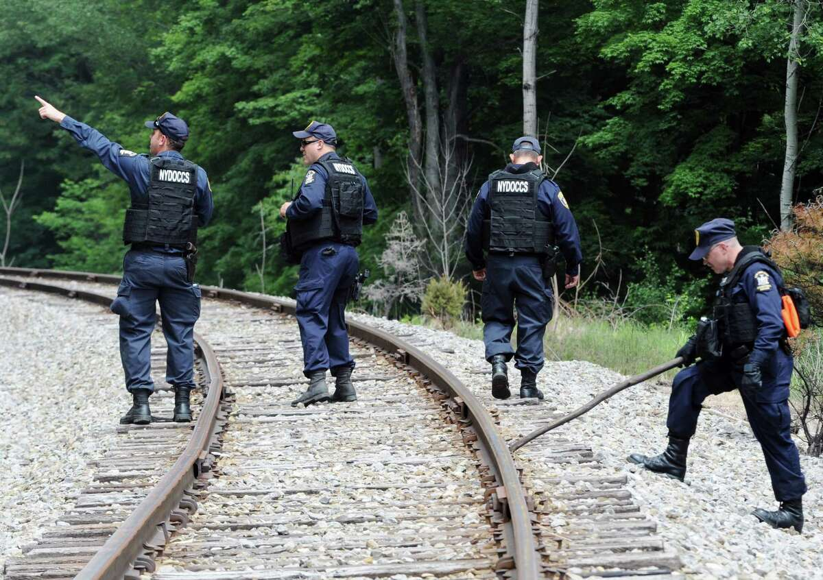 New York State Department of Corrections officers search the railroad tracks after a possible sighting of the two murder convicts who escaped from a northern New York prison two weeks ago on June 21, 2015, in Friendship, N.Y.