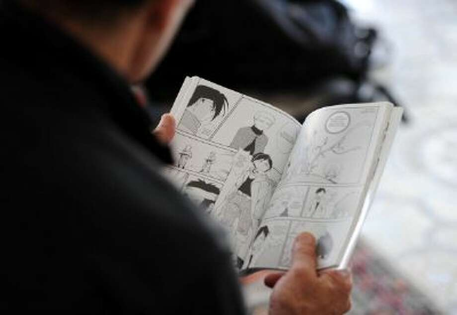 "TO GO WITH AFP STORY - A man reads ""The revolution"" a manga comic book created by Algerian artist, Fella Matougui, for the 50th anniversary of Algeria's independence on September 18, 2013 in Algiers. The DZ (for Algeria) manga comics are a massively popular book form, originally from Japan, that is now flourishing in Algeria as well. AFP PHOTO FAROUK BATICHE (Photo credit should read FAROUK BATICHE/AFP/Getty Images) Photo: AFP/Getty Images / 2013 AFP"