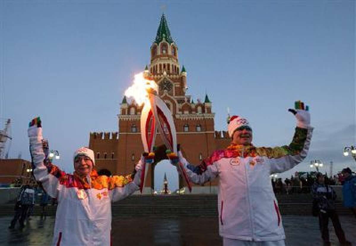 Torch bearers hold their torches during the Olympic torch relay in downtown Yoshkar-Ola, some 600 km ( 372 miles) east of Moscow, Russia.